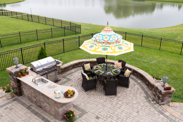 Outdoor living space on a brick patio overlooking a tranquil lake